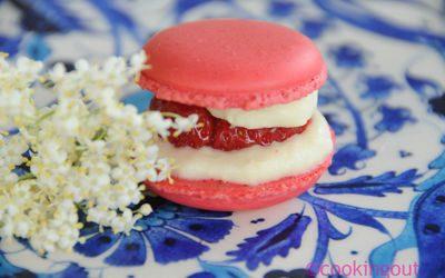 Un joli petit macaron tout rose parfumé à la fraise sur une ganache au sirop de fleurs de sureau.