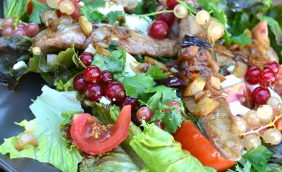 Une salade d'été avec des aiguillettes de canard et des groseilles