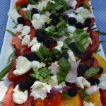 Salade d'été, mélange de fruits et de légumes avec des tomates, mozzarella et mures