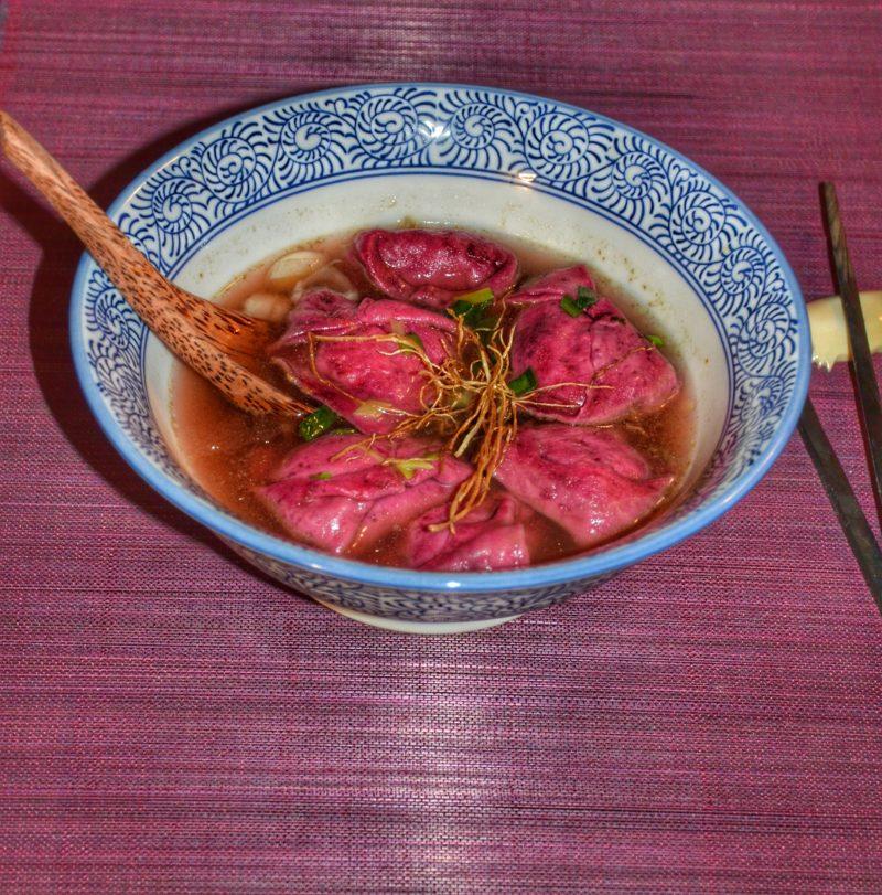 Ravioles roses parfumées à la betterave farcie aux légumes dans un bouillon d'épluchures de légumes