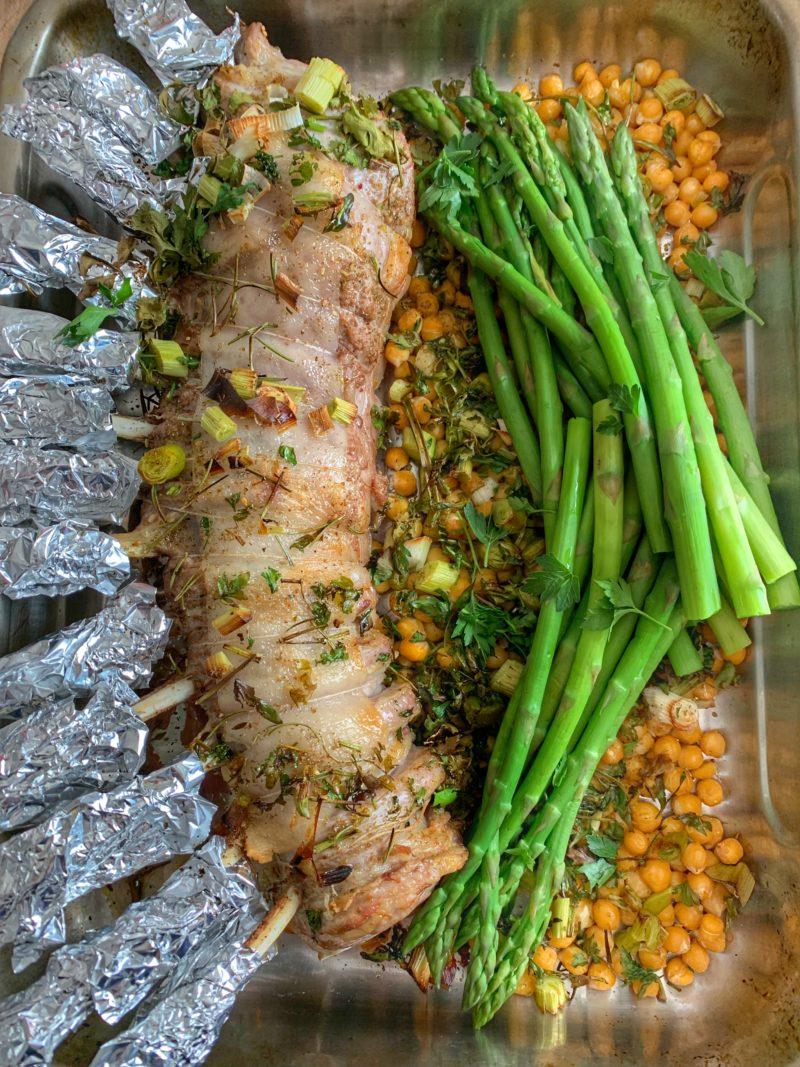 carré d'agneau cuit avec du zaatar, de l'aillet et servi avec asperges et pois chiches grillés