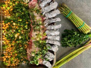 Carré d'agneau avant cuisson avec aillet, persil et asperges vertes