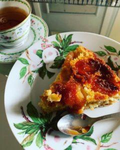 part de gâteau renversé aux abricots secs servi avec son thé